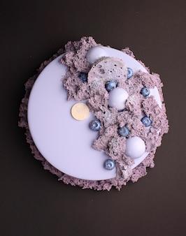 Торт с ежевичным муссом в зеркальной глазури украшен молекулярным бисквитом. на черном фоне.