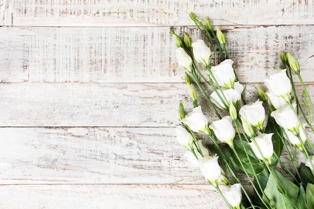 白い花の花束を持つ木製の背景