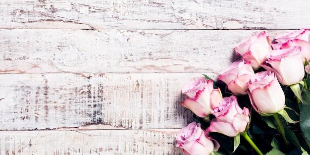 ピンクのバラの花束と木製の背景
