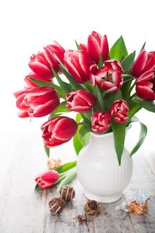 白い背景の上の花瓶にピンクのチューリップの花束