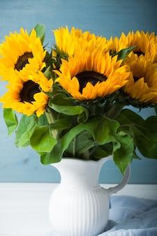 白い花瓶の美しいヒマワリの花束