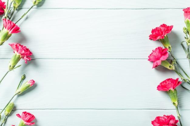 明るいターコイズ色の木製の背景にピンクのカーネーションの花束