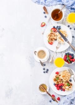 花の形、果実、軽い木製のテーブルの上に蜂蜜のスコッチパンケーキと朝食します。