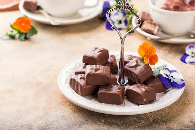 パンジーの花と白い皿の上の柔らかいヌガーチョコレートお菓子。パーティーフードのコンセプトです。