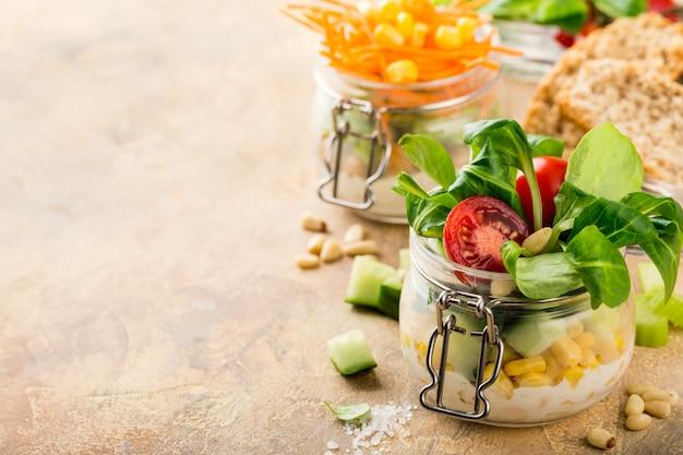 コーンのサラダと野菜のガラス瓶の中の自家製サラダ。