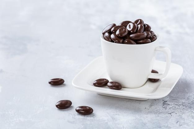 白いコーヒーカップのダークチョコレート菓子