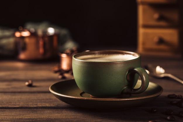 Зеленая чашка кофе с кофемолкой