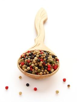 Черный, белый и красный перец специи на деревянной ложкой на белом
