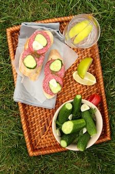 自家製の新鮮な塩漬けキュウリのボウルとスモークソーセージとサンドイッチ