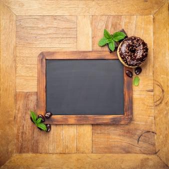 チョコレート艶をかけられたドーナツと黒い黒板