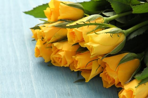 青い背景に黄色のバラの花束