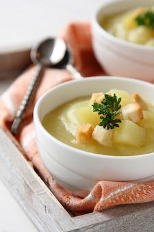 白いボウルにクルトンとパセリのクリーミーなサツマイモのスープ