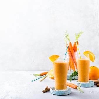 健康的なニンジンのスムージー、オレンジとシナモンのガラス