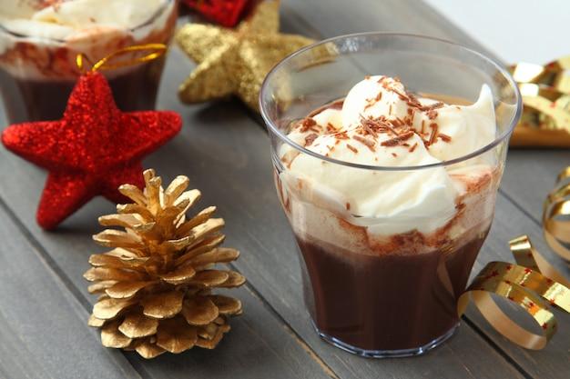 木製のテーブルの上のクリスマスの装飾と新鮮なチョコレートミルクセーキ