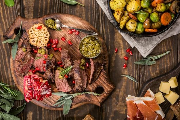 カンガルー肉のステーキ、グリーンペストとザクロの木製まな板の上。