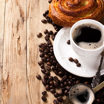 Старый кофейник и чашка на деревянном деревенском фоне
