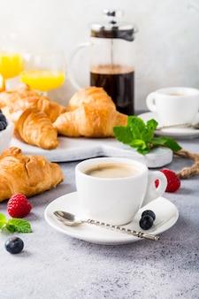 Белые чашки кофе и круассаны