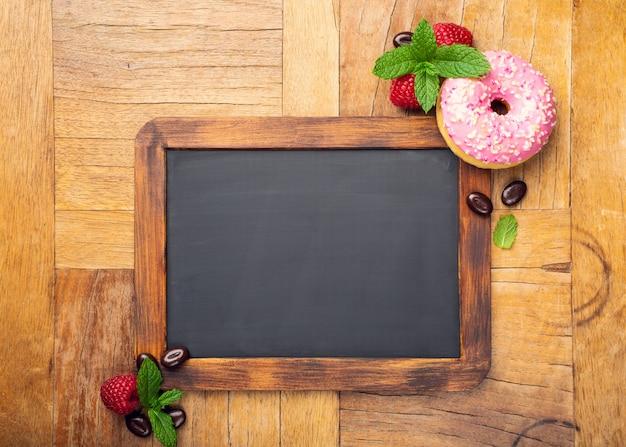 Черная доска с розовым глазированным пончиком