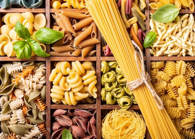 木製の箱で盛り合わせカラフルなイタリアンパスタ