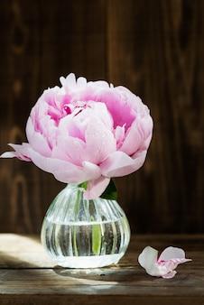 Свежий букет розовых пионов на темном деревенском фоне