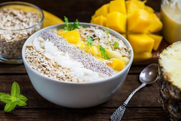 Смузи из манго, банана, ананаса и овсянки в миске