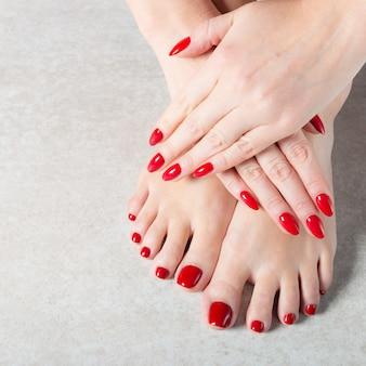 若い女性は彼女の赤いマニキュアの爪を見せています。