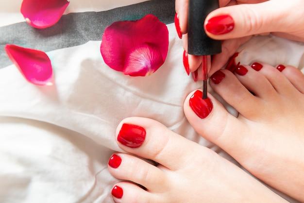 Молодая леди наносит красный лак на пальцы ног