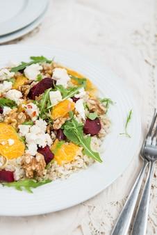 暖かいヘルシーなキノア、玄米、ビートルートとオレンジのサラダ