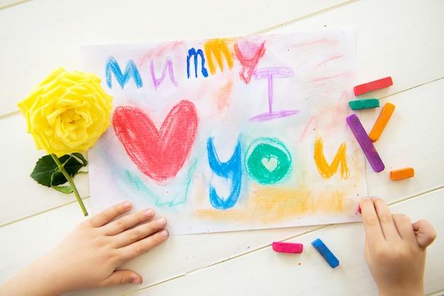 Маленькая девочка рисует открытку ко дню матери