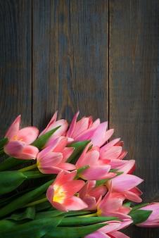 木製の暗い背景にピンクのチューリップの束