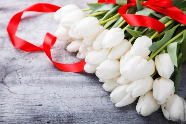 赤いリボンと花束白いチューリップ。