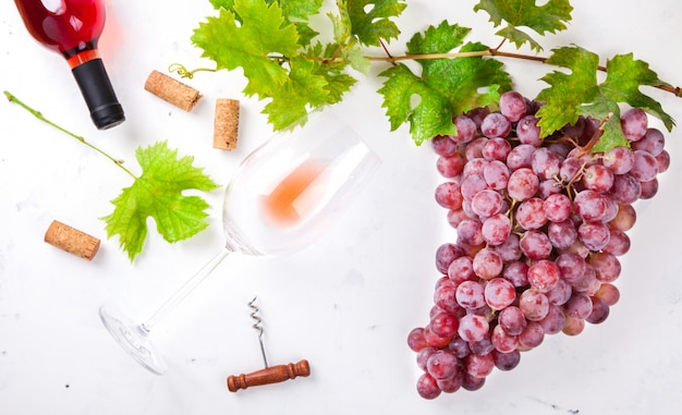 Вино розовое и виноградная гроздь. алкогольный напиток в бокале