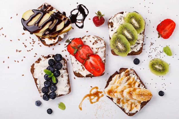 Установите сладкие бутерброды со сливочным сыром и свежими ягодами и фруктами поверх