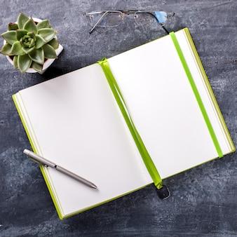 ペン、メガネ、および花のビジネスコンセプトのメモ帳。