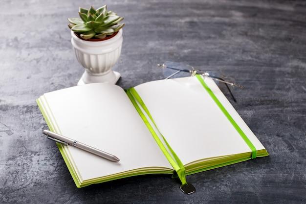 ペン、メガネ、花とメモ帳ビジネスコンセプト