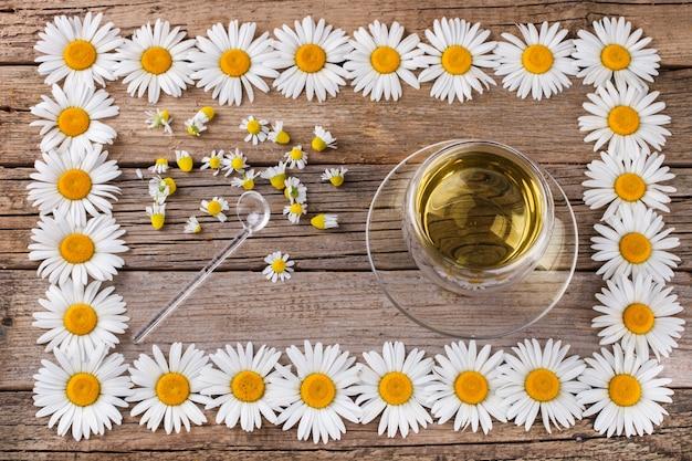 Ромашковый чай на деревянном фоне, в стеклянной чашке