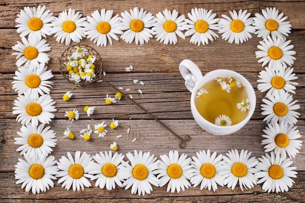 Ромашковый чай на деревянных фоне. в цветочной рамке