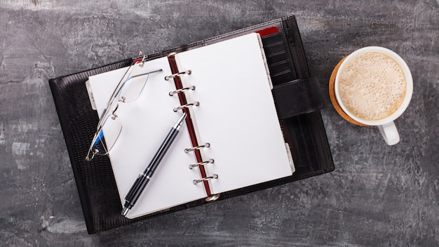 ペン、メガネ、コーヒーのメモ帳ビジネスコンセプト