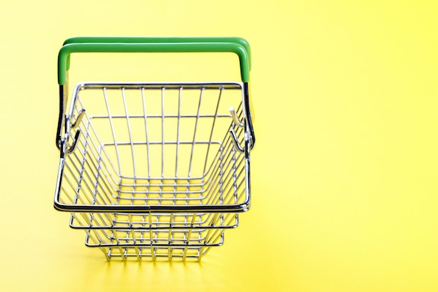 ショッピングバスケットは明るい黄色の背景に空です。