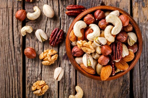 Орехи, смешанные в деревянной тарелке. ассортимент