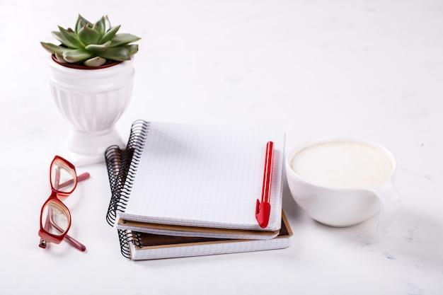 ペン、メガネ、コーヒー、花とメモ帳ビジネスコンセプト