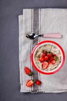新鮮なイチゴとオートミールのお粥。夏の健康的な朝食。