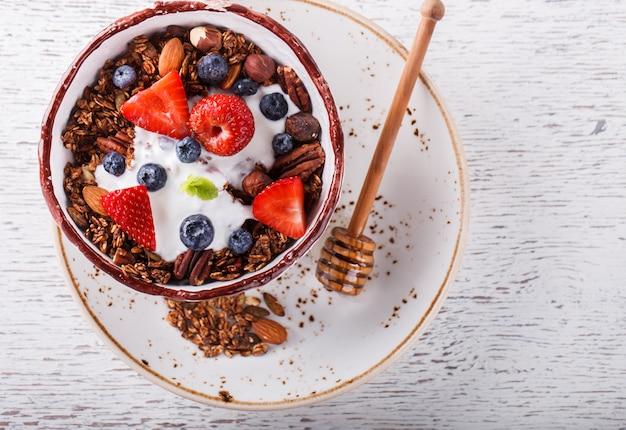グラノーラ、新鮮な果実、ベリーのピューレ。夏の健康的な朝食。