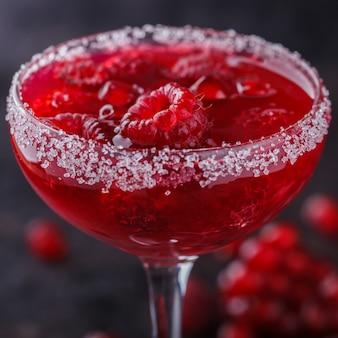 ガラスのガラスのラズベリーとザクロと赤のアルコールカクテル。セレクティブフォーカス