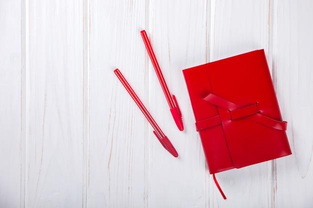 Блокнот красный с ручкой бизнес-концепция