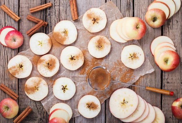 古い木製の背景にシナモンでスライスしたリンゴ