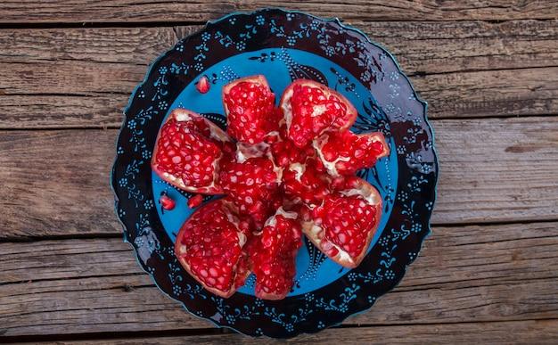 青いプレートに熟したザクロの果実