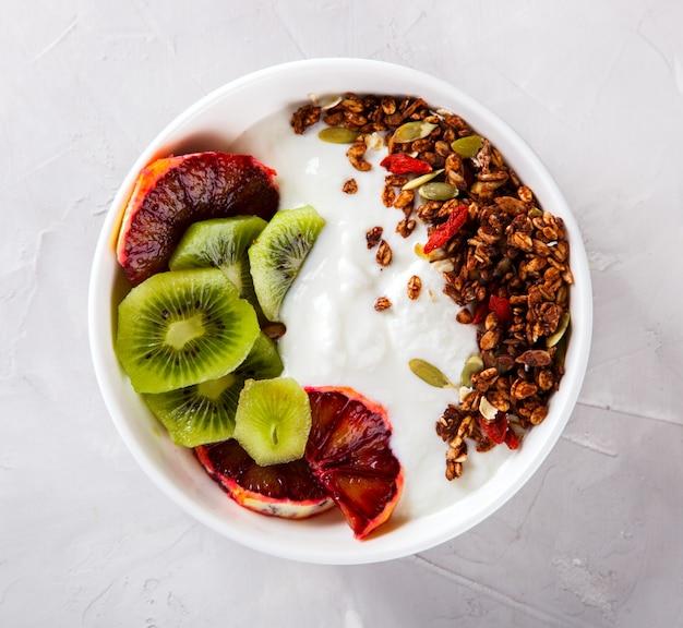 Гранола, йогурт с киви и красными апельсинами. завтрак полезен
