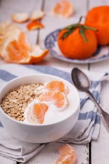 ヨーグルトとマンダリン入りのオートミール。健康的な朝食