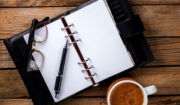 ペン、グラス、コーヒーとノート